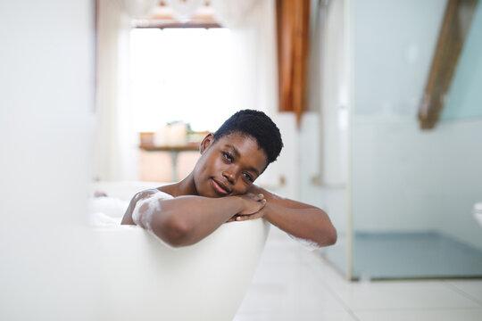 Portrait of smiling african american woman in bathroom, relaxing in bath