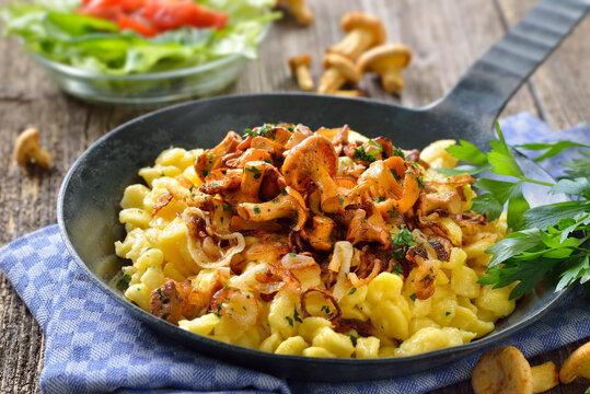 Schwäbische Spätzle mit  frischen, gebratenen Pfifferlingen und Zwiebeln in der Pfanne rustikal serviert - Vegetarian Swabian spaetzle with fried chanterelles and onions served in a frying pan