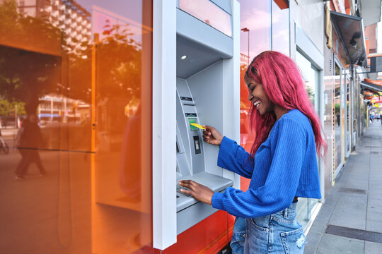 Black woman using ATM machine in city