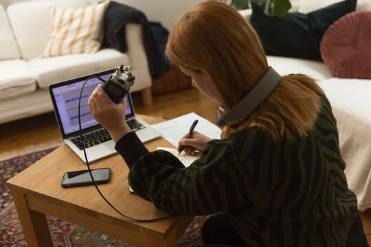 Woman taking notes and preparing for recording podcast