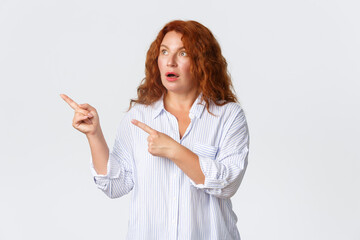 Portrait of impressed and speechless redhead middle-aged woman drop jaw, gasping wondered as...