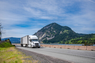 Powerful industrial white big rig semi truck with grille guard transporting frozen cargo in reefer semi trailer driving on highway road with river and mountain on the side