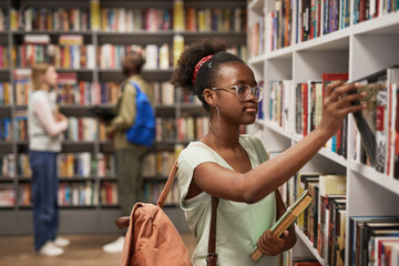 Obraz Waist up portrait of female Africa-American student choosing books in college library, copy space - fototapety do salonu