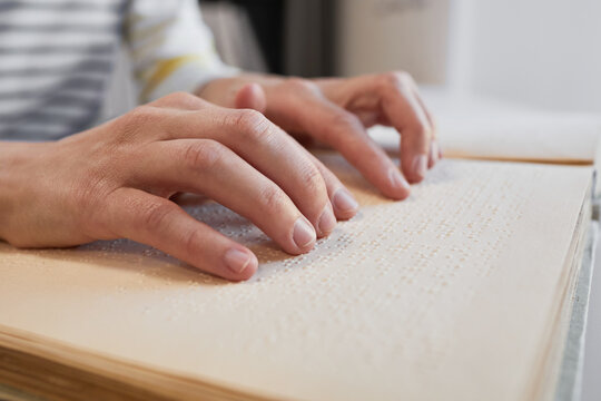 Close up of unrecognizable man reading Braille book in college library, copy space