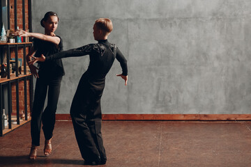 Young couple in black dancing ballroom dance Paso Doble