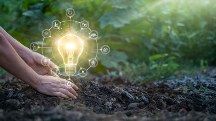Hands of men touching leaf and glowing light bulb on the soil. Symbol. Against nature on green leaf background with icons energy sources for renewable, sustainable development. Ecology concept.
