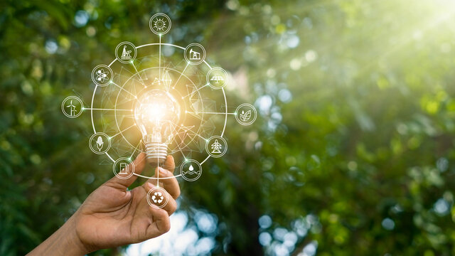 Hand holding light bulb against nature on green forest with icons energy sources for renewable, sustainable development. Ecology and environment concept.