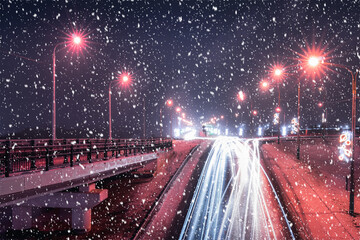 Traces of headlights from cars moving at winter night on the bridge in a snowfall. Lights reflecting in the wet asphalt.