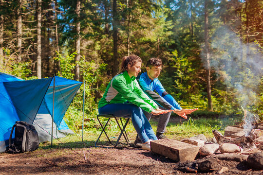 Young couple of travelers enjoy campfire in summer forest. Tourists sitting by tent warming hands. Camping in woods