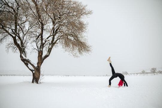 Woman doing yoga in One Legged Wheel pose in winter