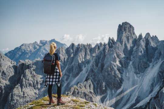 Woman hiker with backpack against Cadini di Misurina mountain group range of Italian Alps, Dolomites, Italy, Europe
