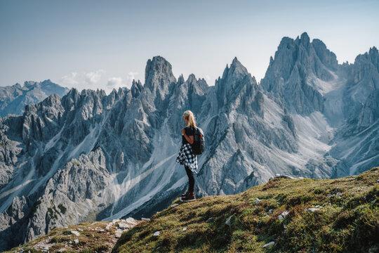 Woman hiker with backpack enjoying Cadini di Misurina mountain group range of Italian Alps, Dolomites, Italy, Europe