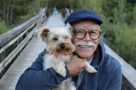 Ethnic senior man with small dog in the park