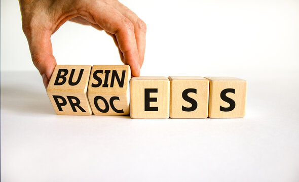Success business process symbol. Businessman turns wooden cubes with words 'business process'. Beautiful white background, copy space. Success business process concept.