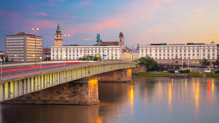 Linz, Austria. Panoramic cityscape image of riverside Linz, Austria during twilight blue hour with reflection of the city lights in Danube river.