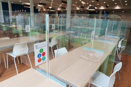 Salle de cantine / restaurant d'entreprise avec des cloisons en plexiglas, plaques de protection contre la propagation du coronavirus pendant la pandémie de covid 19 (France)