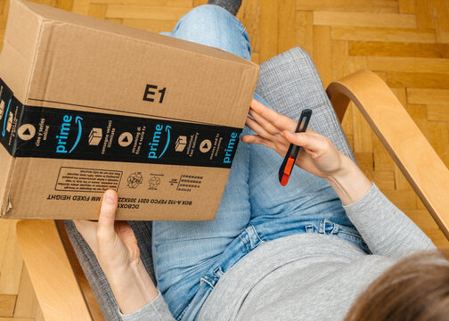 PARIS, FRANCE - NOV 4, 2017: Woman unpacking on the living room armchair the Amazon Prime large cardboard box with Prime scotch sealing tape