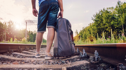 Fototapeta man in shorts and sneakers stands on railway and holding road ba obraz