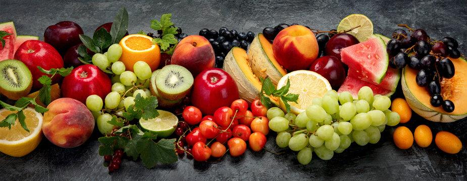 Assorted fresh fruits on dark background.