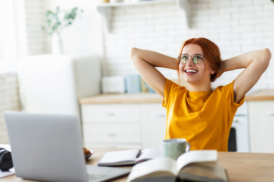 Caucasian red haired girl looks away and ponders of plans for the future, beautiful young student woman, throwing your hands behind your head, resting after online education, lecture or webinar