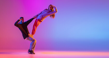 Flyer. Two young people, guy and girl dancing contemporary dance, hip-hop over pink background in neon light.