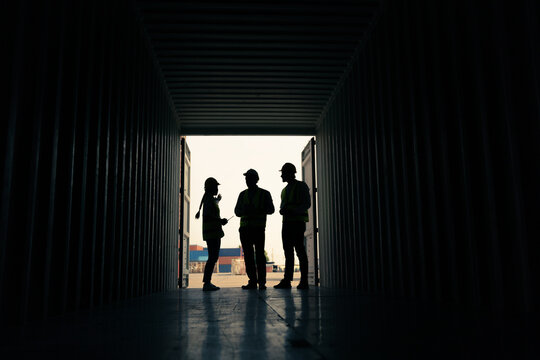 silhouette Group of staff worker standing and checking the containers box from cargo ship for export and import