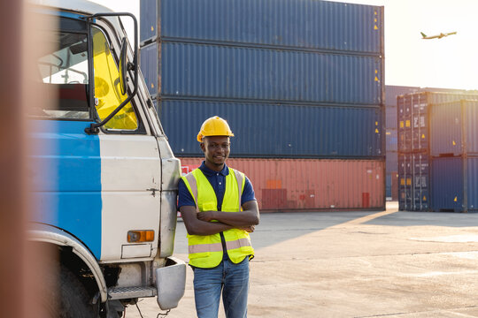 An African truck driver stood resting and smiling happily beside the truck. at the container warehouse