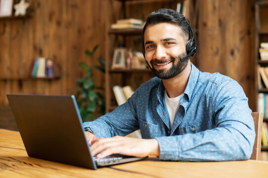 Smiling Indian male freelancer wearing headset and smart casual wear using laptop for connection with colleagues or customers, talking online sitting in the home office and looks at the camera