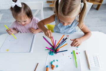 high angle view of preschooler girl and toddler kid with down syndrome drawing in kindergarten