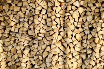 Heap of chopped firewood in pile close-up. Firewood storage close up. Stock of wooden logs. Chopped wood in bright sunlight. Rustic lifestyle. Woodpile with firewood full frame image. Wooden texture.