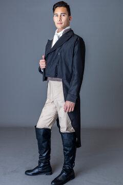 A Regency gentleman standing against a studio backdrop