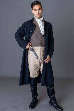 A Regency gentleman holding a flintlock pistol against a studio backdrop