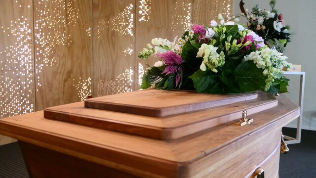 closeup shot of a funeral casket or coffin in a hearse or chapel or burial at cemetery
