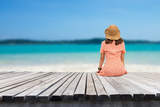 Summer beach vacation concept, Asia woman with hat sitting on wood floor on the beach look at the beauty of the white sandy beach, sea and sky. She felt happy and relaxed when she came to the beach.