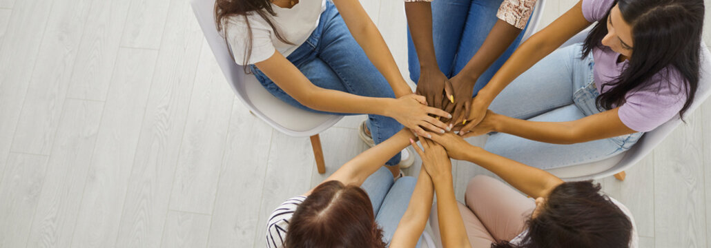 Banner background with overhead view of group of five beautiful modern young women sitting in circle and holding hands. Concept of team aiming for one goal together, unity, support, helping each other