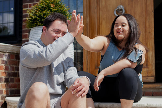 Young biracial couple with Down Syndrome in active wear and wearable tech high-fiving