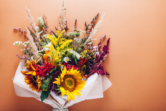 Fall bouquet of yellow red orange flowers wrapped in paper and arranged on background. Sunflowers, zinnias and grasses
