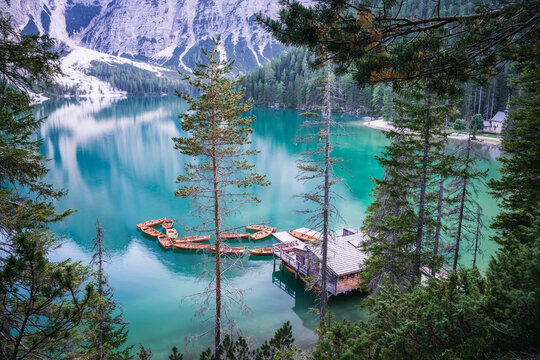 Boathouse and wooden boats at Braies or Pragser Wildsee during sunset pink light. Dolomites, Italy