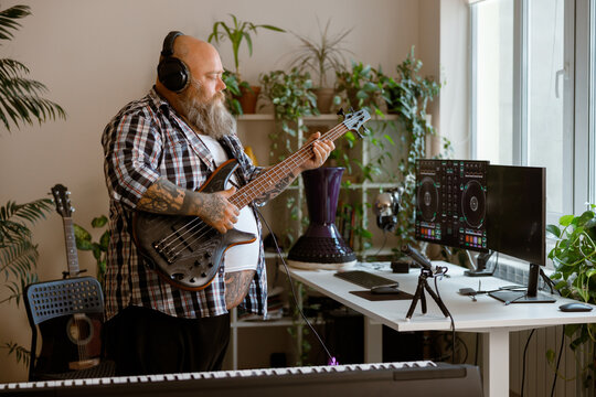 Obese man with long beard plays bas guitar recording new song in home studio
