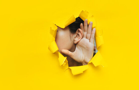 Close-up of a woman's ear and hand through a torn hole in the paper. Yellow background, copy space. The concept of eavesdropping, espionage, gossip and tabloids.