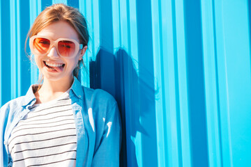 Obraz Young beautiful smiling hipster woman in trendy summer clothes. Sexy carefree woman posing on the street background near blue wall at sunset. Positive model outdoors. Cheerful and happy in sunglasses - fototapety do salonu