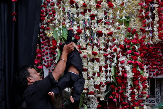 """A Shi'ite Muslim holds a child to touch """"Taziya"""" during a Muharram procession marking Ashura in Ahmedabad"""