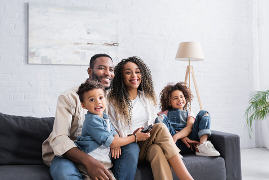 happy african american family watching comedy on couch at home