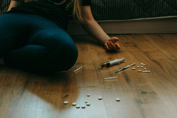 Addict woman with syringe and drugs on the floor. Substance abuse, drugs addiction concept.