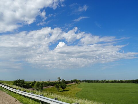 Altocumulus castellanus clouds over a green field of hay. Kansas Flint Hills.