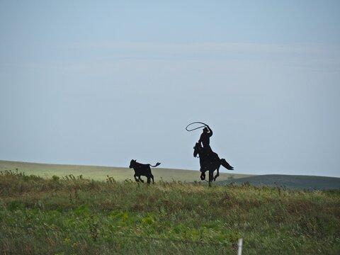 Metal sculpture of cowboy lassoing a cow in the Flint Hills of Kansas.