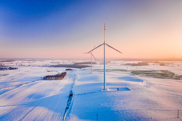 Wind turbine on winter snowy field. Alternative energy, Poland