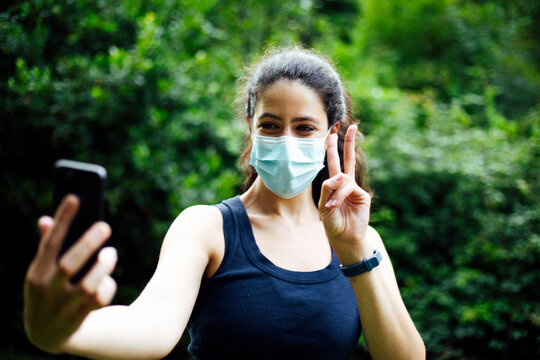 Beautiful smiling fit sportswoman with mask taking a selfie and showing peace gesture