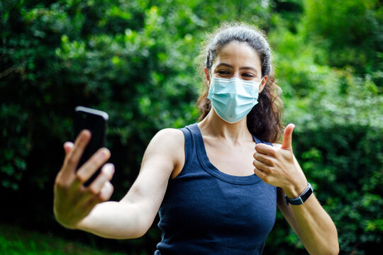 A young caucasian woman wearing a mask with phone taking selfie