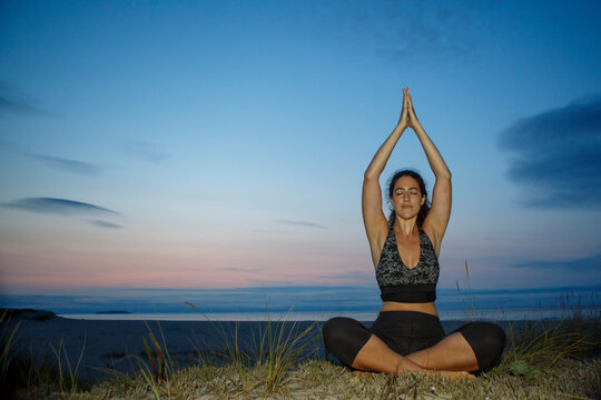 Silhouette of young woman practicing yoga on the beach